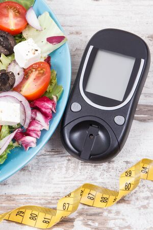 Glucometer, tape measure and fresh greek salad with feta cheese and vegetables. Best healthy food for diabetics, dieting and slimming 写真素材