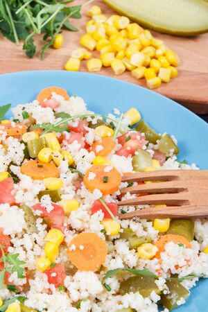 Fresh prepared salad with couscous and vegetables. Healthy light dietary vegan meal Stock Photo