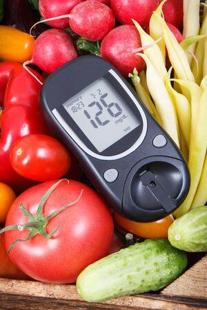 Glucómetro para controlar el nivel de azúcar y las verduras frescas maduras como ingredientes saludables que contienen vitaminas y minerales que se utilizan durante la diabetes.