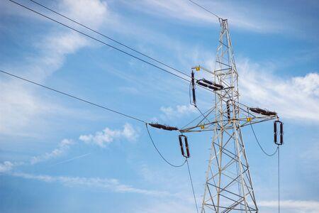 Elektrischer Hochspannungsmast mit Drähten auf Hintergrund des blauen Himmels. Linie der Stromübertragung und -verteilung