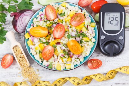 Glucometer for analyzing sugar level and fresh salad with bulgur groats and vegetables. Diabetes, slimming and healthy lifestyles and nutrition concept