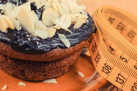 Tape measure and fresh baked homemade muffin with coffee, chocolate and almonds. Delicious dessert and slimming concept Standard-Bild