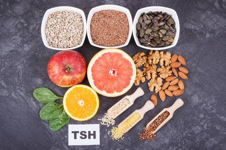 Inscription TSH with nutritious products and ingredients containing vitamins and minerals for healthy thyroid Stock Photo