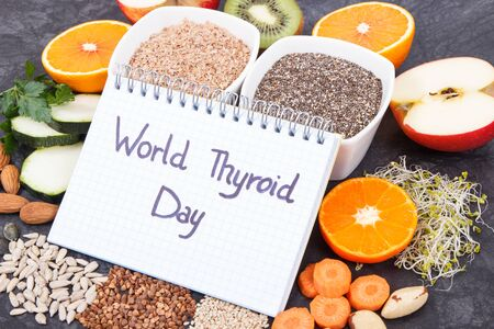 Nutritious ingredients and inscription World Thyroid Day written in notepad. Healthy food containing vitamins. Problems with thyroid concept