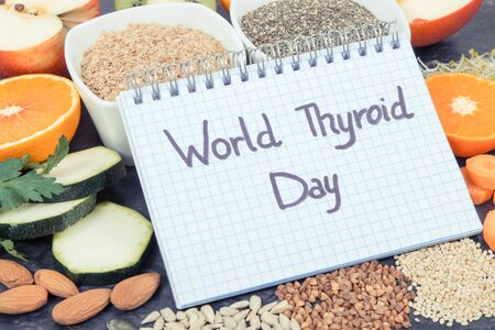 Notepad with inscription World Thyroid Day and best food containing natural minerals and vitamins for healthy thyroid Stock Photo