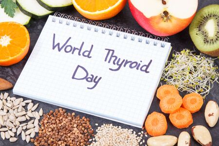 Notepad with inscription World Thyroid Day and best nutritious ingredients for healthy thyroid Stock Photo