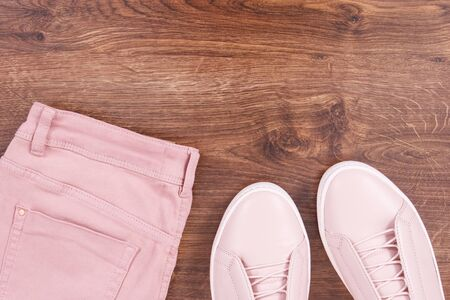 Womanly pink leather shoes and cotton pants, copy space for text on rustic boards
