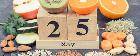 Nutritious healthy food and May 25 on cube calendar as date of World Thyroid Day. Problems with thyroid concept. Ingredients containing natural vitamins and minerals