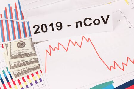 Inscription 2019-nCoV, currencies dollars and downward graphs representing financial crisis caused by Covid-19.