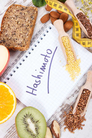 Notepad with inscription hashimoto, tape measure and best nutritious ingredients or products for healthy thyroid Reklamní fotografie