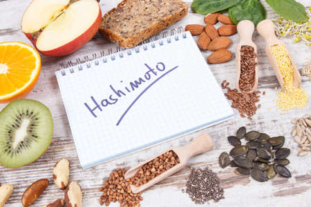 Notepad with inscription hashimoto and best ingredients or products for healthy thyroid. Food containing natural minerals and vitamins
