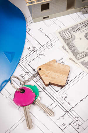 Keys with home shape, currencies dollar and house under construction on electrical construction drawings for engineering jobs. Building or buying home concept. Technology