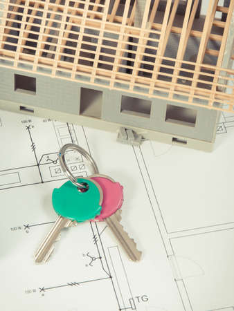 Home keys, house under construction and electrical diagrams for engineer jobs