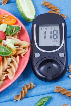 Glucometer with result of sugar level and fresh prepared salad with wholegrain pasta and vegetables. Healthy meal containing natural vitamins and minerals