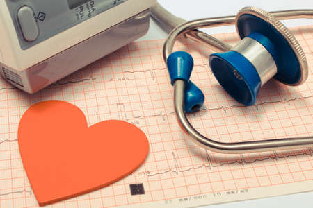 Medical stethoscope, heart shape and equipment for measuring blood pressure on electrocardiogram graph. Ekg heart rhythm. Medicine and healthy lifestyles Archivio Fotografico