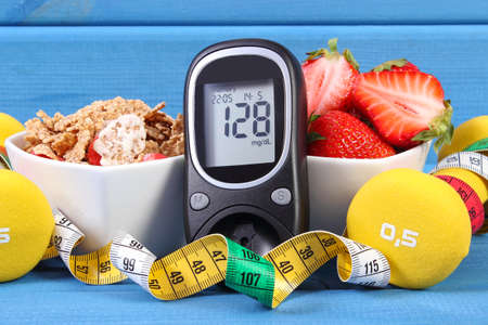 Glucose meter with result of measurement sugar level, healthy food, dumbbells for fitness and tape measure, concept of diabetes, slimming, healthy lifestyle