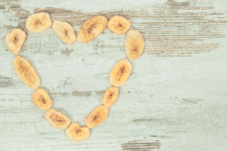 Heap of dried organic banana chips in shape of heart as natural snack for dessert