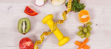 Fresh fuits and vegetables, dumbbell for fitness and tape measure, concept of nutritious food, healthy lifestyles and slimming 免版税图像