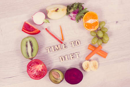 Inscription time to diet and fresh nutritious fruits and vegetables in shape of clock, healthy lifestyle and nutrition concept