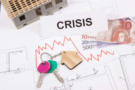Keys of home, currencies euro, downward graphs and inscription crisis on electrical construction diagrams. Real estate crisis