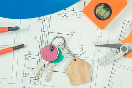 Keys with house shape and electrical construction drawings with work tools for engineering jobs. Building home cost. Technology