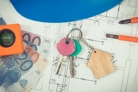 Keys with house shape, currencies euro and electrical construction drawings with work tools for engineering jobs. Building or buying home concept. Technology
