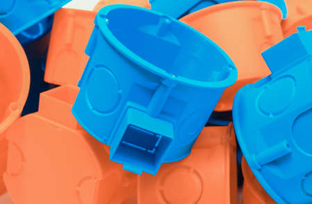 Orange and blue electrical boxes. Components using in electrical installations. Accessories for engineering work