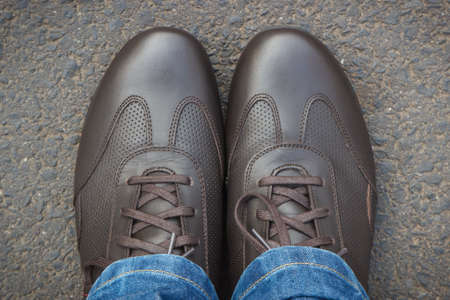 Comfortable casual brown leather shoes for men on asphalt road or footpath. Male footwear