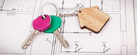 Keys with home shape on electrical construction diagrams of house. Concept of building or buying home