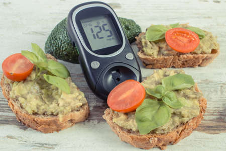 Glucose meter for checking and measuring sugar level and fresh sandwiches with paste of avocado. Healthy food as source omega acids, natiral vitamins and minerals