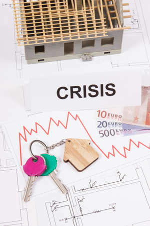 Home keys, inscription crisis, currencies euro and downward graphs representing crisis of real estate market caused by coronavirus. Reduced housing prices. Small house under construction