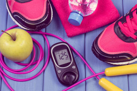 Glucose meter with result of sugar level, pair of sport shoes and accessories for fitness. Diabetes and healthy sporty lifestyles