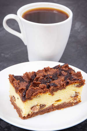 Piece of fresh baked cheesecake on white plate and black coffee. Delicious dessert for different occasion
