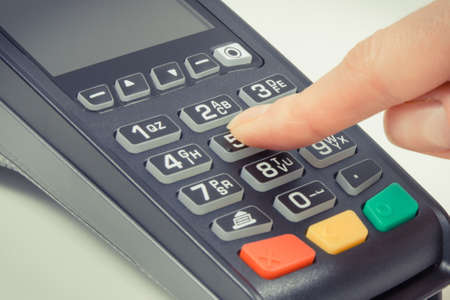 Hand of woman using credit card reader to enter PIN code. Cashless paying. Finance and banking concept Foto de archivo