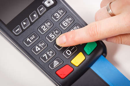 Payment terminal and finger entering PIN code. Credit card reader using for cashless paying. Finance concept