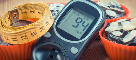 Glucose meter for checking and measuring sugar level, fresh baked chocolate muffins and tape measure. Diabetes, slimming and dessert for different occasions