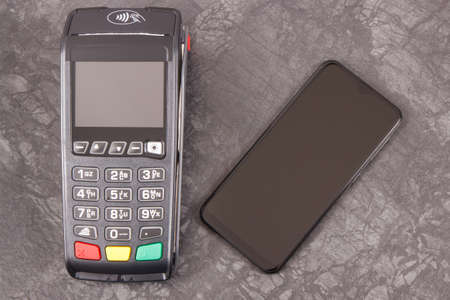 Hand of woman using payment terminal and smartphone to cashless paying. Finance and banking concept