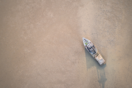 ship wreck: Big old fishing boat standing in the mud sea. Aerial view from flying drone Stock Photo