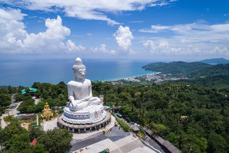 Groot wit Boeddhabeeld bovenop de berg met blauwe hemel in Phuket