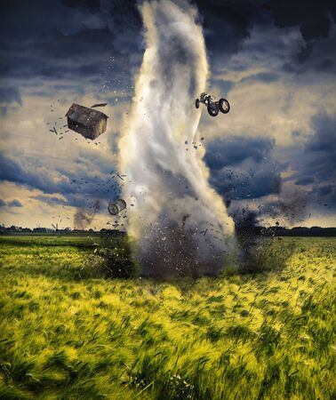 A powerful tornado spins over a corn field and creates destruction in a stormy landscape 写真素材