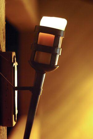 wall sconce: Vela en un candelabro de pared de hierro wroght Foto de archivo