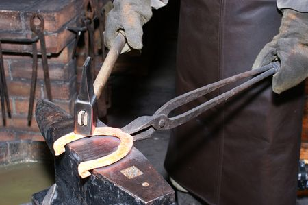 The smith in a smithy forges a horseshoe photo