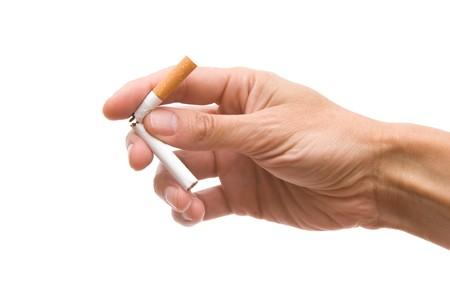 cigarrillos: Cigarrillos en una mano sobre el blanco