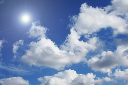 The midday sun in the dark blue sky with white clouds Stock Photo - 7638084