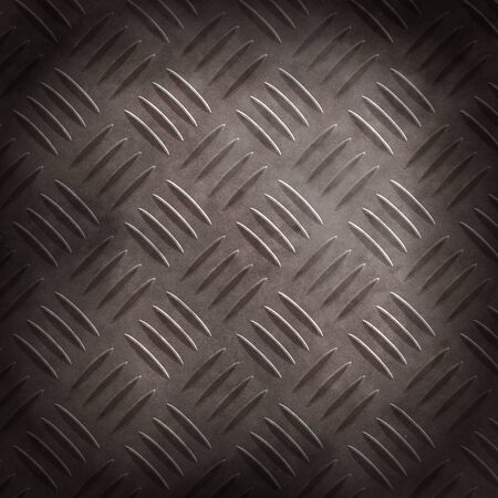 Dark dirty corrugated metal surface illuminated in the center