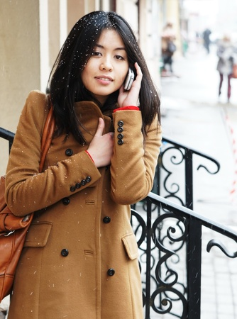 The beautiful Asian girl speaks by phone Stock Photo - 9209029