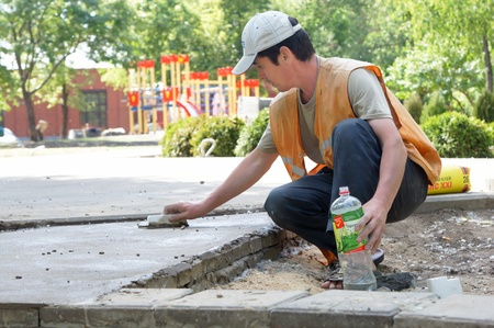 MOSCOW - JUNE 07:  Workers perform works on improvement of court yard on JUNE 07, 2011 in Moscow  By plans of the government of Moscow till September, 1st, 2011 all court yard should be ordered. Stock Photo - 10052126