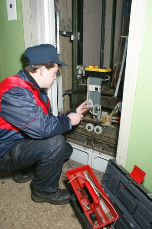 master: The master repairs the lift equipment in an apartment house Editorial