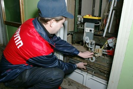 The master repairs the lift equipment in an apartment house
