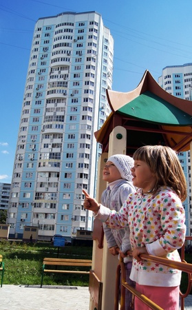 Playing children on a playground against new high apartment houses in Moscow